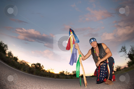 Indigenous man in the middle of a road with ceremonial pole and stock photo, Indigenous man kneeling in the middle of a road with ceremonial pole representing seven directions by Scott Griessel
