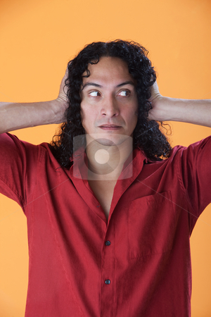 Handsome man covering his ears with his hands stock photo, Handsome curly haired man covering his ears with his hands by Scott Griessel