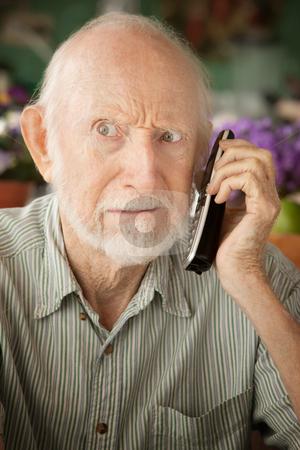 Grumpy senior man on telephone stock photo, Grumpy senior man at home on the telephone by Scott Griessel