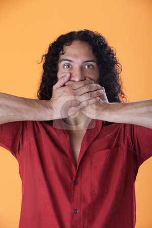 Handsome man covering his mouth with his hands stock photo, Handsome curly haired man covering his mouth with his hands by Scott Griessel