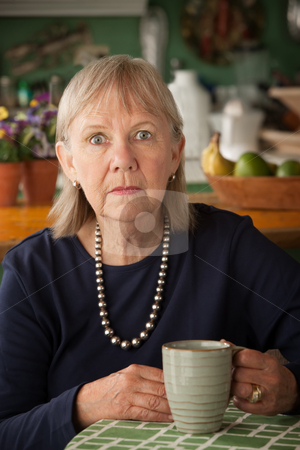 Depressed senior woman with mug stock photo, Depressed senior woman at home with coffee or tea by Scott Griessel