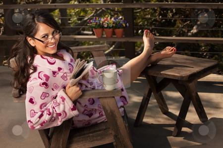 Pretty Hispanic Woman in Bathrobe with Tea or Coffee stock photo, Pretty Hispanic Woman in Bathrobe Sitting Outdoors with Tea or Coffee by Scott Griessel