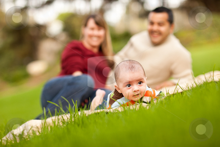 Happy Baby Boy and Mixed Race Parents Playing in the Park stock photo, Happy Crawling Baby Boy and Mixed Race Parents Playing in the Park. by Andy Dean