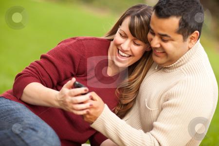 Attractive Mixed Race Couple Enjoying Their Camera Phone stock photo, Attractive Mixed Race Couple Enjoying Their Camera Phone in the Park. by Andy Dean