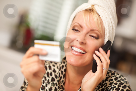 Smiling Robed Woman on Cell Phone With Credit Card stock photo, Smiling Robed Woman on Cell Phone Looking At Her Credit Card. by Andy Dean