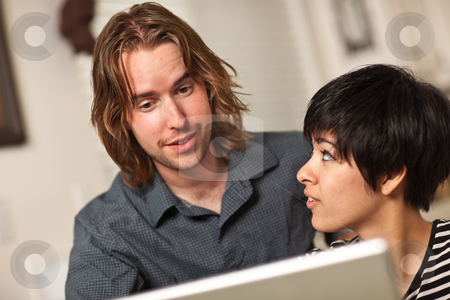 Happy Young Man and Woman Using Laptop Together stock photo, Happy Young Caucasian Man and Multiethnic Woman Using the Laptop Computer Together. by Andy Dean