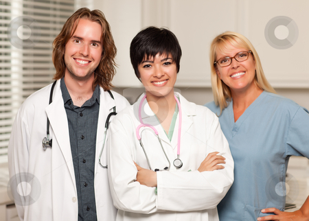 Three Smiling Male and Female Doctors or Nurses stock photo, Three Smiling Male and Female Doctors or Nurses in the Office. by Andy Dean