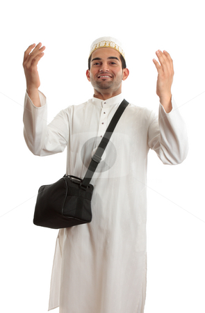 Ethnic man with arms raised in praise stock photo, Ethnic mixed race man wearing white embroidered robe  and topi hat and carrying black shoulder bag and arms raised in praise or joy by Leah-Anne Thompson