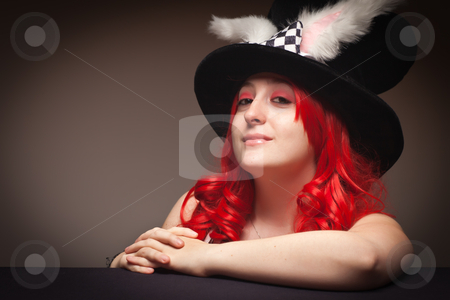 Attractive Red Haired Woman Wearing Bunny Ear Hat stock photo, Attractive Red Haired Woman Wearing Bunny Ear Hat on a Grey Background. by Andy Dean