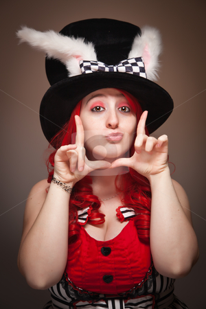 Attractive Red Haired Woman Wearing Bunny Ear Hat Framing Face stock photo, Attractive Red Haired Woman Wearing Bunny Ear Hat and Framing Her Face with her Hands on a Grey Background. by Andy Dean