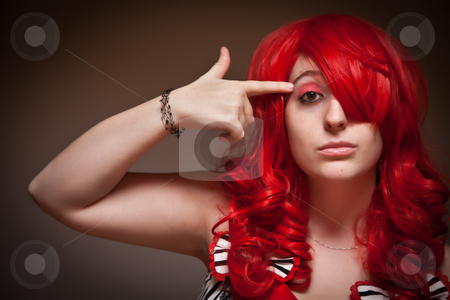 Attractive Young Red Haired Woman with Hand To Her Head  stock photo, Portrait of an Attractive Red Haired Woman with Hand in the Shape of a Gun to Her Head on a Grey Background. by Andy Dean
