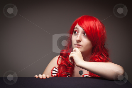 Attractive Red Haired Woman Portrait stock photo, Portrait of an Attractive Red Haired Woman Looking Up with Her Hand on Chin on a Grey Background. by Andy Dean