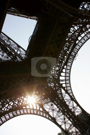 Eiffel tower sunshine stock photo, Sun shining through underside of Eiffel tower, Paris, France. by Martin Crowdy