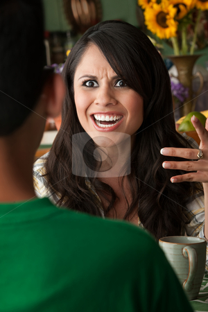 Angry Latina Woman with Cofee or Tea and Male Companion stock photo, Angry Latina Woman at table in Kitchen with Coffee or Tea and Male Companion by Scott Griessel