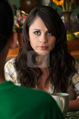 Serious Latina Woman with Cofee or Tea and Male Companion stock photo, Serious Latina Woman at table in Kitchen with Coffee or Tea and Male Companion by Scott Griessel