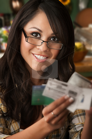 Beautiful Latina Woman with Coupons stock photo, Beautiful Latina Woman at table in Kitchen with Coupons by Scott Griessel