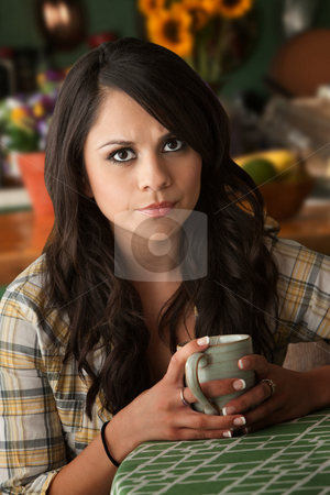 Beautiful Serious Latina Woman with Cofee or Tea stock photo, Beautiful Sad or Serious Latina Woman at Table in Kitchen with Coffee or Tea by Scott Griessel