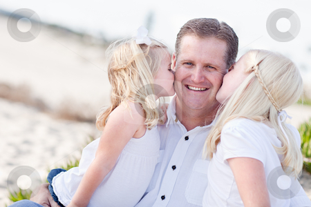 Handsome Dad Getting Kisses from His Cute Daughters  stock photo, Handsome Dad Getting Kisses from His Cute Daughters at The Beach. by Andy Dean