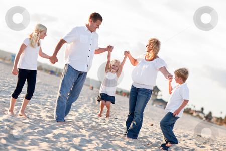 Adorable Little Girl Swinging with Her Parents stock photo, Adorable Little Girl Swinging with Her Parents and Family at the Beach. by Andy Dean