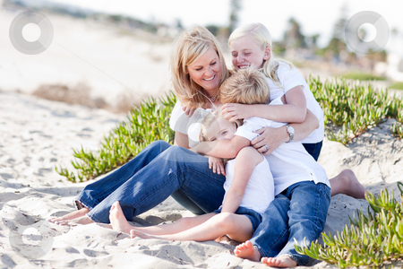 Attractive Mom Having Fun with Her Cute Children stock photo, Attractive Mom Having Fun with Her Cute Children at The Beach. by Andy Dean