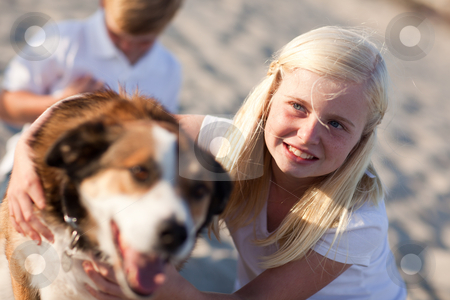 Cure Girl Playing with Her Dog stock photo, Cure Girl Playing with Her Dog at the Beach. by Andy Dean
