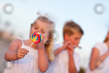 Cute Brother and Sisters Enjoying Their Lollipops Outside stock photo, Cute Brother and Sisters Enjoying Their Lollipops at the Beach - Focus is on the Lollipop. by Andy Dean