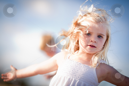 Adorable Blue Eyed Girl Playing Outside stock photo, Adorable Blue Eyed Girl Playing Outside with Her Family. by Andy Dean