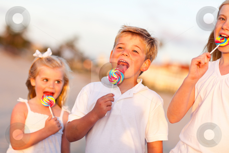 Cute Brother and Sisters Enjoying Their Lollipops Outside stock photo, Cute Brother and Sisters Enjoying Their Lollipops at the Beach. by Andy Dean