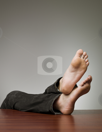 Feet on the table stock photo, Lazy man with his feet at the table by Anne-Louise Quarfoth