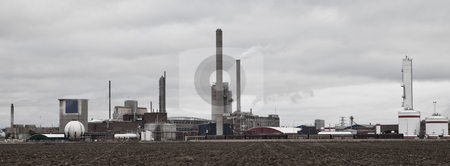 Industrial buildings behind a field  stock photo, Industrial buildings behind a field on a cloudy day by Anne-Louise Quarfoth