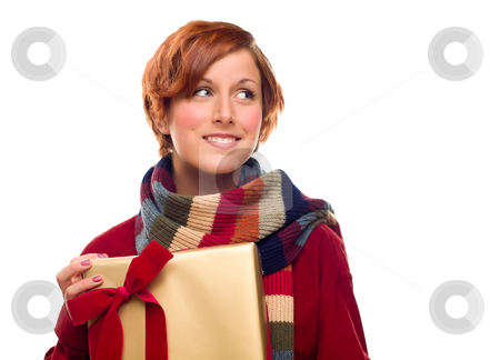 Pretty Girl with Gift Looking to the Side Isolated stock photo, Pretty Red Haired Girl with Scarf Holding Wrapped Gift Looking Off to the Side Isolated on a White Background. by Andy Dean