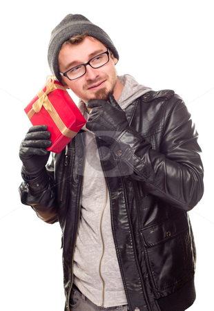 Warmly Dressed Young Man Holding Wrapped Gift To His Ear stock photo, Warmly Dressed Handsome Young Man Holding Wrapped Gift To His Ear Isolated on a White Background. by Andy Dean