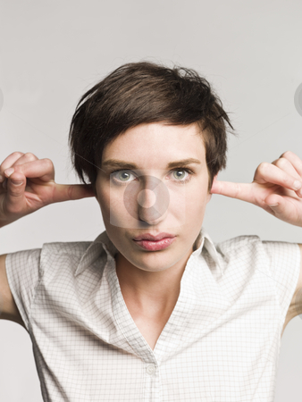 Portrait of a woman with fingers in her ears stock photo, Portrait of a woman with fingers in her ears by Anne-Louise Quarfoth