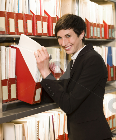 Smiling woman searching at an archive stock photo, Smiling woman searching at an archive by Anne-Louise Quarfoth