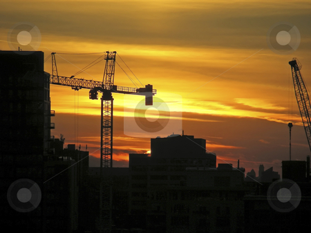 City Sunset stock photo, Construction equipment against the orange clouds of a spectular city sunset. by Mary Lane