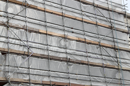 Building covered in scaffolding and tarpaulin for renovation. stock photo, Building covered in scaffolding and tarpaulin for renovation. by Stephen Rees