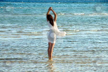 Woman in white dress and raised hands standing in blue sea water