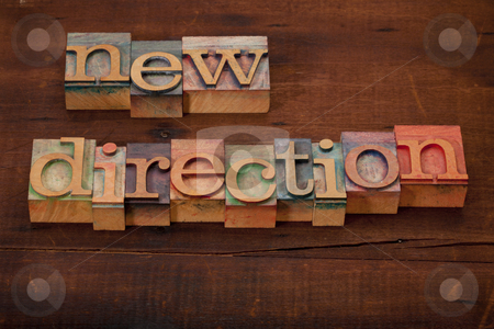 New direction concept stock photo, New direction words in vintage wooden letterpress printing blocks on old scratched and cracked wood by Marek Uliasz