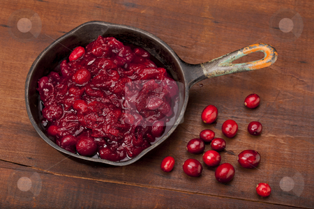 Frying cranberries stock photo, Freshly fried cranberry sacuce on a small iron pan and some fresh berries against old scratched wooden table top by Marek Uliasz