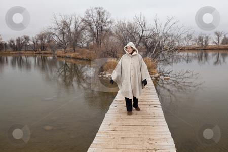 Senior woman enjoys a walki alone stock photo, Senior woman in her eighties walking alone on a footbridge across lake, nostalgic late fall scenery, life pathway metaphor by Marek Uliasz