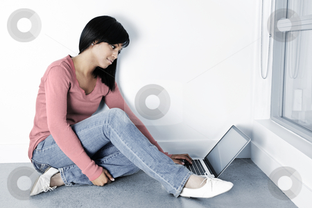 Young woman using laptop computer on floor stock photo, Black woman with computer sitting on floor and typing by Elena Elisseeva