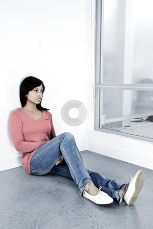 Depressed woman sitting on the floor stock photo, Depressed black woman sitting against wall looking out window by Elena Elisseeva