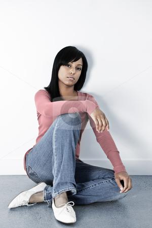 Depressed woman sitting on the floor stock photo, Depressed black woman sitting on the floor against wall by Elena Elisseeva