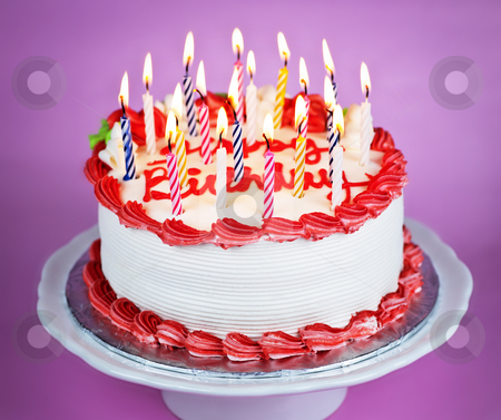 Birthday cake with lit candles stock photo, Birthday cake with burning candles on a plate on pink background by Elena Elisseeva