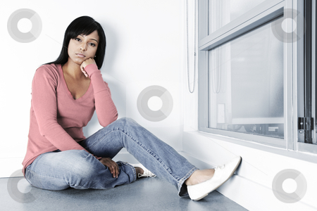 Depressed woman sitting on floor stock photo, Sad young black woman sitting against wall on floor by Elena Elisseeva