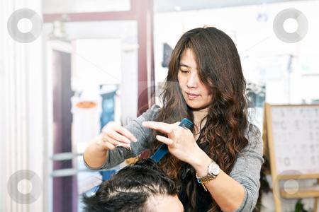 Hair stylist working stock photo, Happy hairdresser cutting hair in her salon by Elena Elisseeva