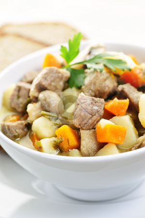 Bowl of beef stew stock photo, Bowl of hearty beef stew with vegetables served with rye bread by Elena Elisseeva