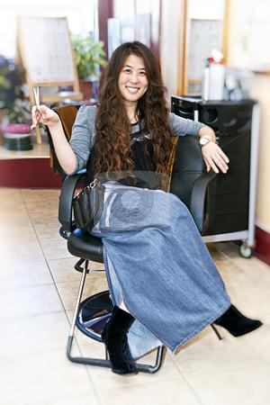 Hair stylist in salon stock photo, Hairstylist sitting in a chair in her hair salon by Elena Elisseeva