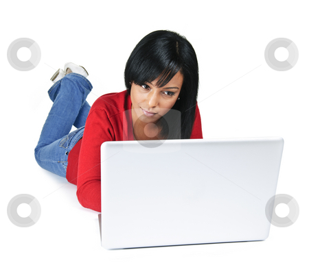 Young woman with laptop computer stock photo, Black young woman typing on computer laying on floor by Elena Elisseeva