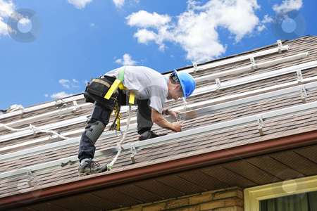Man working on roof installing rails for solar panels stock photo, Man installing rails for solar panels on residential house roof by Elena Elisseeva